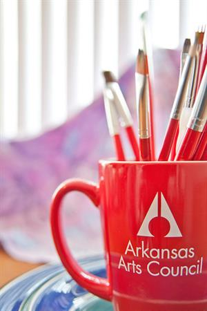 red mug with arkansas arts council logo and paintbrushes inside