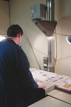 man standing over a microfilm
