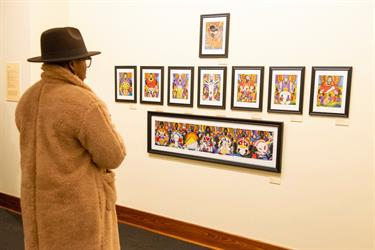 person in coat and hat looking at wall display of art images
