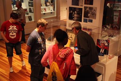 children and adult looking at exhibits in glass cases