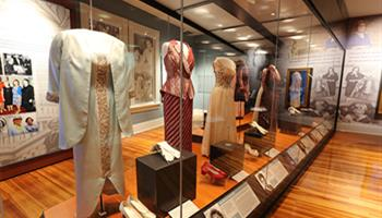 historic dresses in glass display cases in center of exhibit